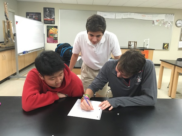 Science Olympiad club founders Zachary Boroughs and Kevin Jung work with club member junior Johnny Coudsi.