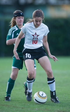 Sophomore Gracie Firestone dodges an opponent as she takes the ball down the field during the team's match against Awty International, Nov. 19. The team won 2-0.