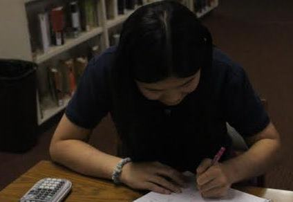 A student studies for the math competition in the library.