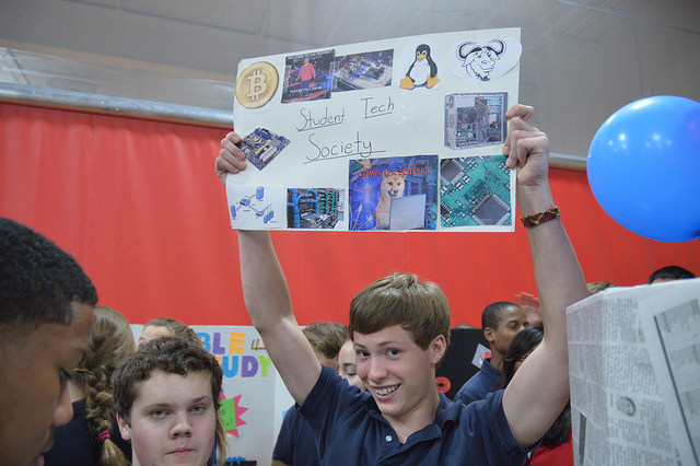 Junior Reed Brace holds his sign for Student Tech Society high above the crowd.