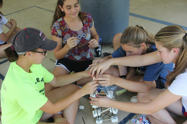 Freshmen and peer leaders build a tower out of marshmallow and toothpicks.