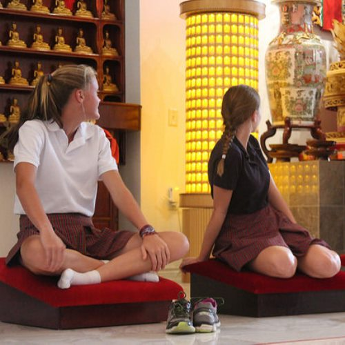 Freshmen learn to meditate on cushions at the Buddhist temple. They were told to meditate for ten seconds while smiling.