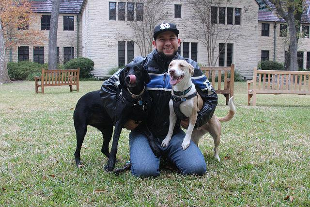 Photography teacher Chuy Benitez with Ruby, the black lab, and Sally, the mutt