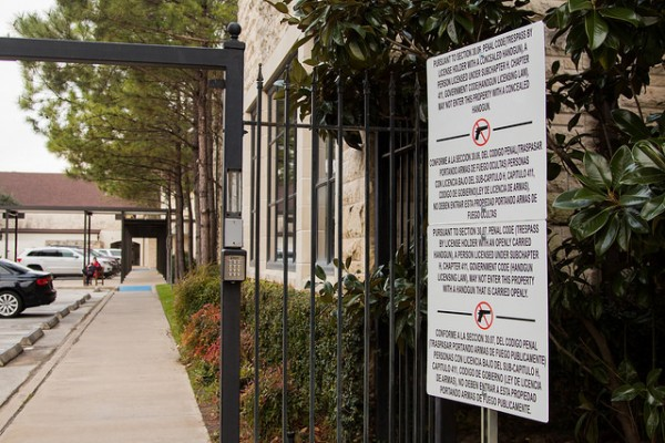 A 30.06 sign stating school gun policy is posted on a gate to campus.