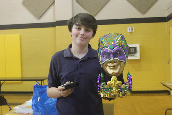 Freshman Clyde Johnson presents the remote-controlled sculpture he made of a Mardi Gras Mask. This year's Symposium theme was