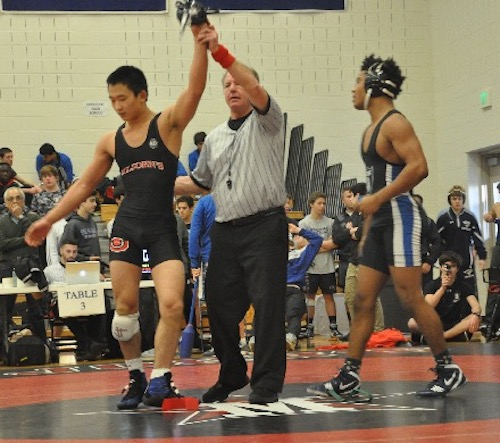 Yo Akiyama, left, has his hand raised after winning by pin in the first round of the state tournament against an opponent from Episcopal High School. Akiyama won the tournament and was named most outstanding wrestler.