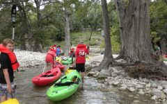 Freshmen trudge their kayaks along shallow water and rocky paths.