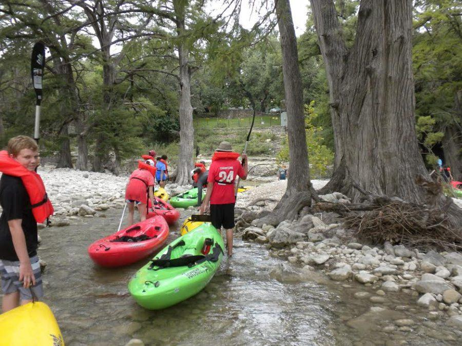 Freshmen+trudge+their+kayaks+along+shallow+water+and+rocky+paths.