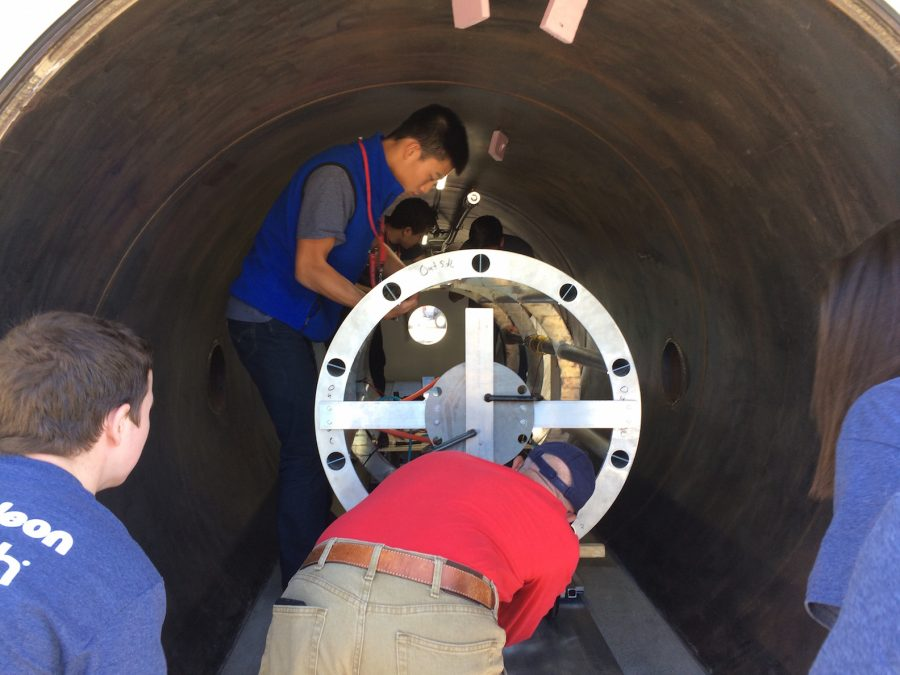 From left: senior Robert Gottschalk, junior Michael He (far back), adviser Franco Posa and junior Elizabeth Award test the pod in a vacuum chamber to ensure that its electronics would not overheat.
