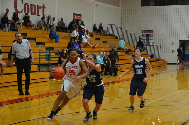 Sophomore Lena McZeal dribbles past a Village defender.