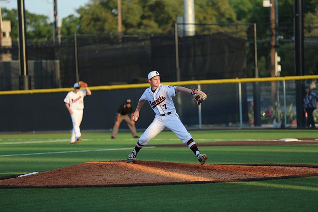 Freshman Beckett Vine winds up to pitch against St. Pius.