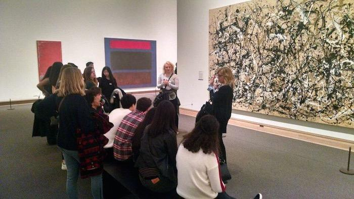 The class observes work by Jackson Pollock, an American artist known for his unique style of drip-painting.