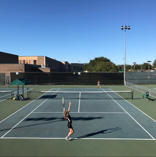 Girls tennis member Hannah Johnston plays singles against Stratford. Although boys tennis is making cuts, girls tennis has a total of 32 girls players on Varsity and JV, including one senior on JV.