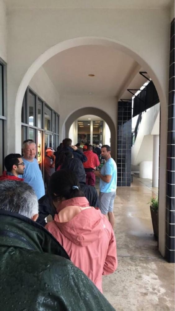 After a lull in the rain, the line for a grocery store stretches outside.