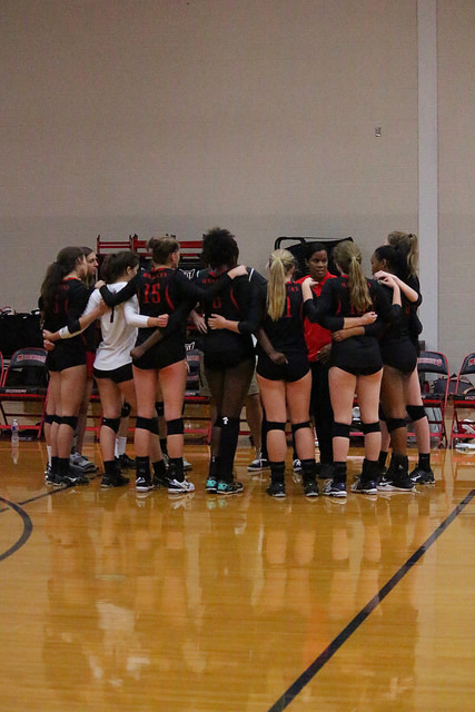 Girls' volleyball huddles after a game.