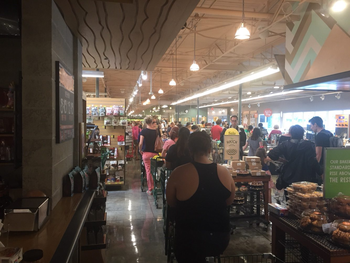 The line at Whole Foods (?) stretches out to the back of the store.
