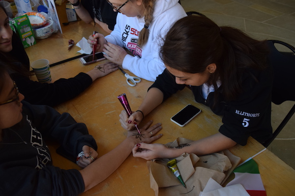 Junior Caitlin Ellithorpe puts a henna design on a student's hand at the India booth.