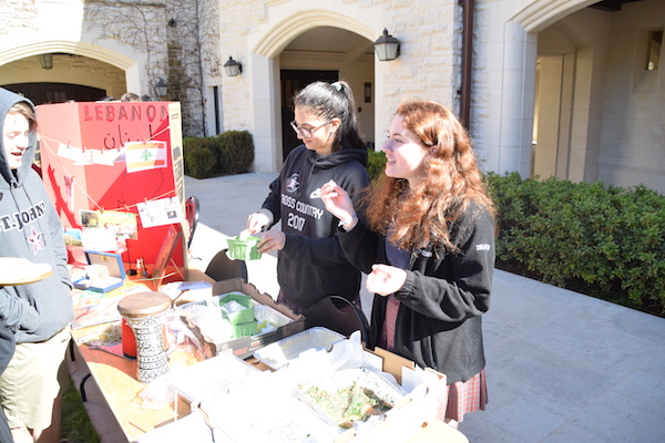 Sophomore and International club co-leader Mia Fares (left) and junior Juliette Draper serve food at the Lebanon booth.