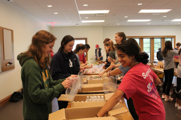 Sophomores place water bottles in care packages, which were distributed to Homeless  Heart locations.
