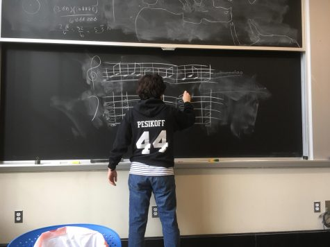 Junior Ethan Pesikoff works on a musical problem on the chalkboard.