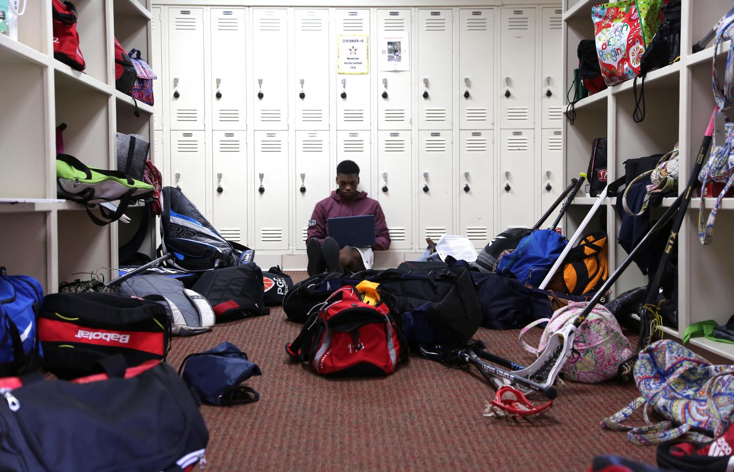 Sophomore Aloye Oshotse works amidst the bags strewn across the hallway.