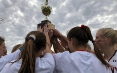 The field hockey team lifts their SPC trophy.