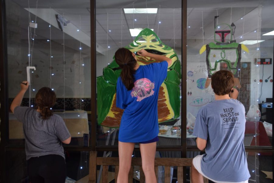 Students decorate the Senior Country windows to celebrate this year's Kinkaid Week theme: space!