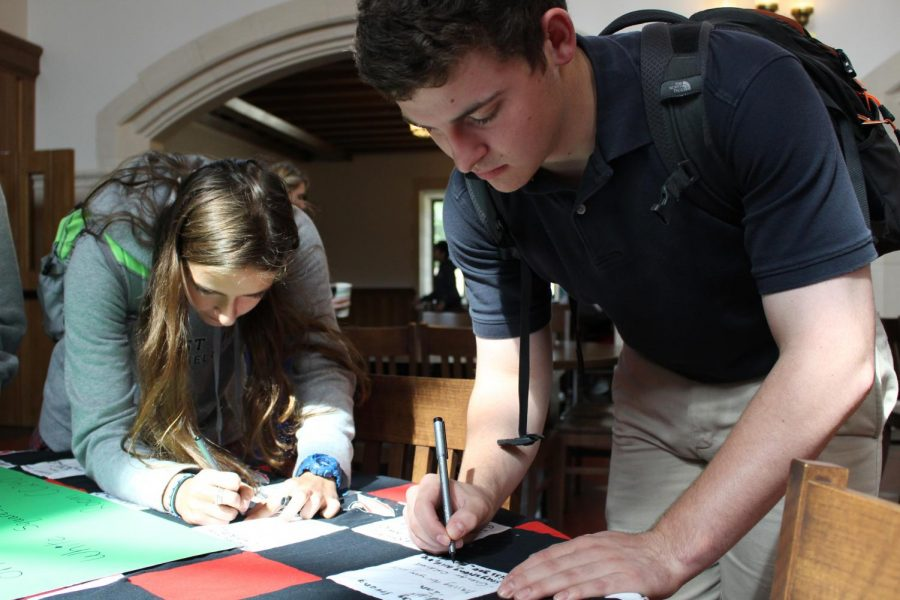 Juniors Sofia Castore and Beckett Vine write well-wishes on a quilt made by Community Service Coordinator Marci Bahr. The quilt will be delivered to McKone in the hospital when all space is filled up.