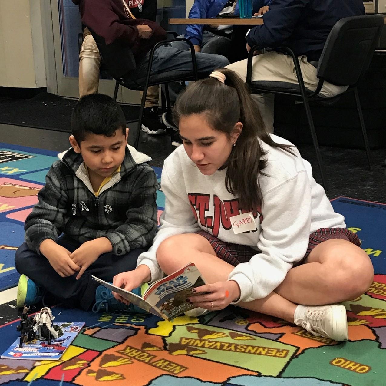 Freshman Gaby Jammar reads books to children at the Nehemiah Center.