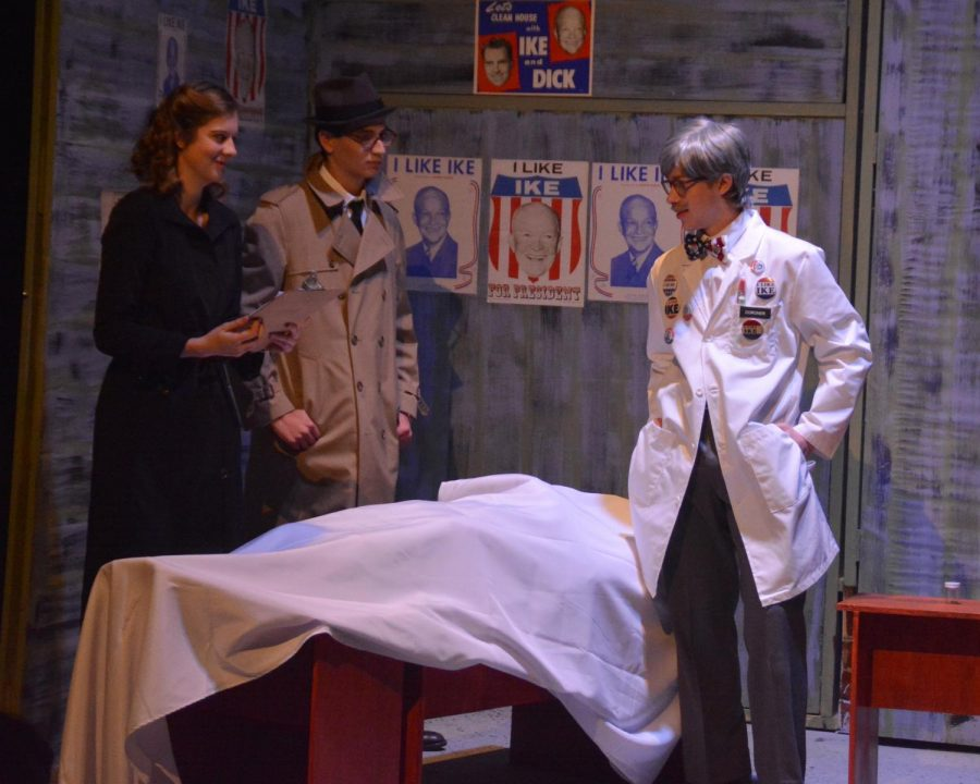 Maggie Pelletier (played by Sacha Waters) and Frank Keller (played by Eli Maierson) examine the results of the autopsy conducted by the doctor (played by George Hagle).