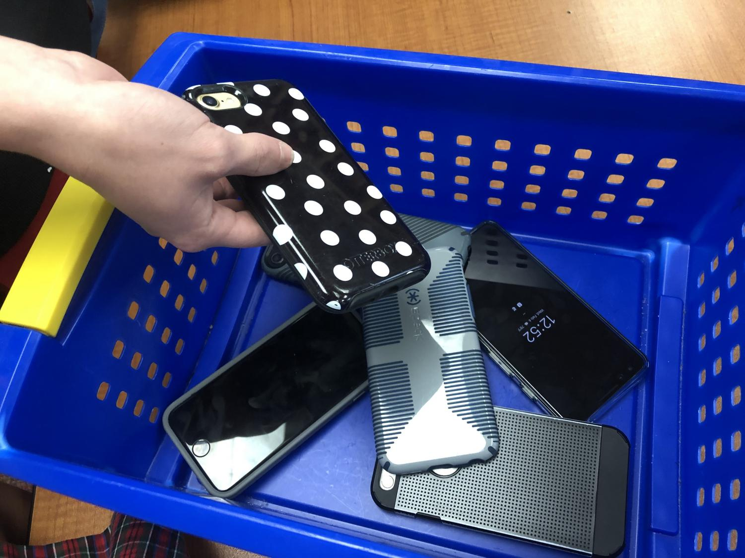 Students placing their phones in a collection box before class.