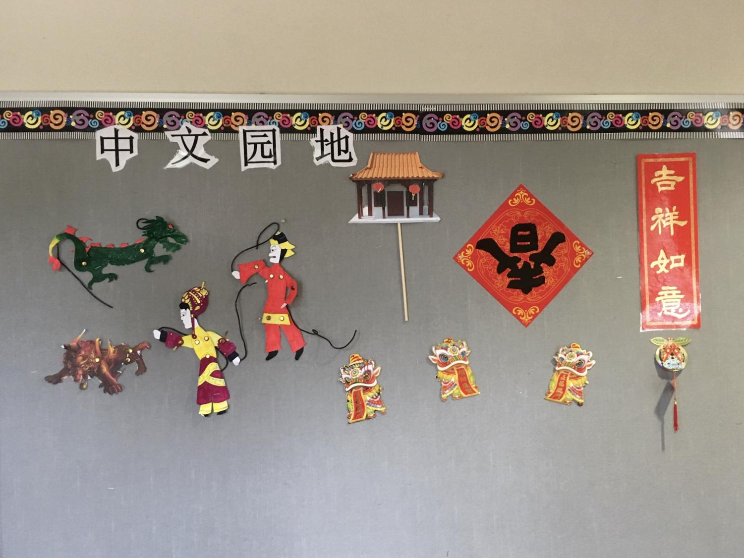 Traditional shadow puppets and other decorations line the wall outside Chinese teacher Jing Nan Gea's classroom for the Lunar New Year.