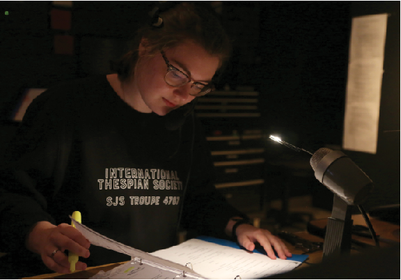 Stage manager Lucy Curtis works in the sound booth, following along in her script as actors run scenes in Lowe Theater. As stage manager, she organizes the show's cast, gives backstage cues and facilitates communication between director and the set crew.