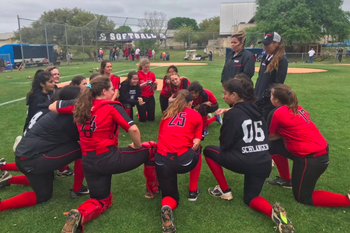 The softball team huddles up after their undefeated weekend.