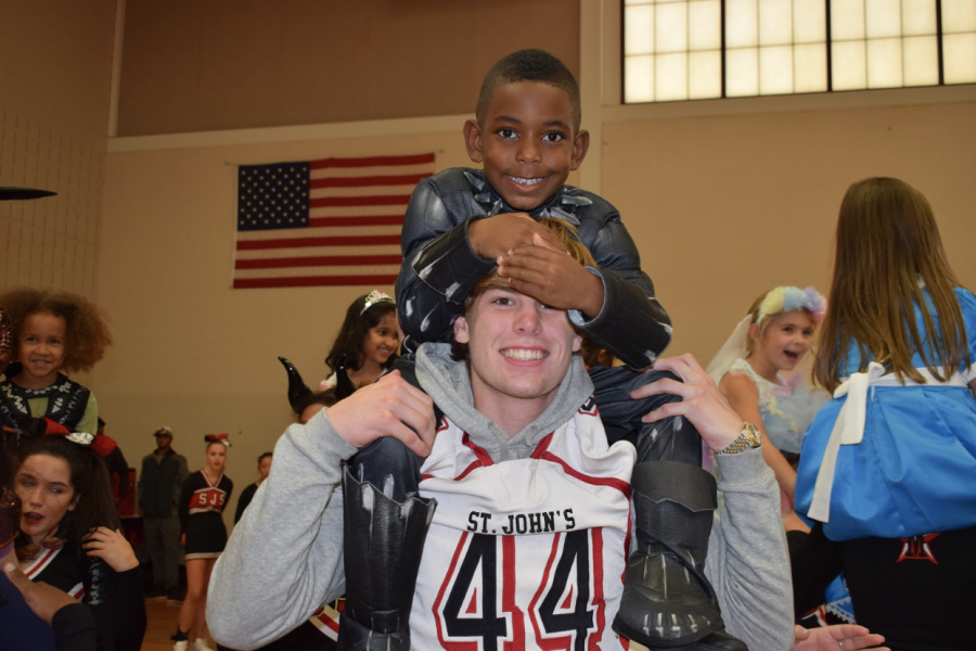 Sophomore John Avery Fouch carries a kindergartner dressed as Black Panther on his shoulders.