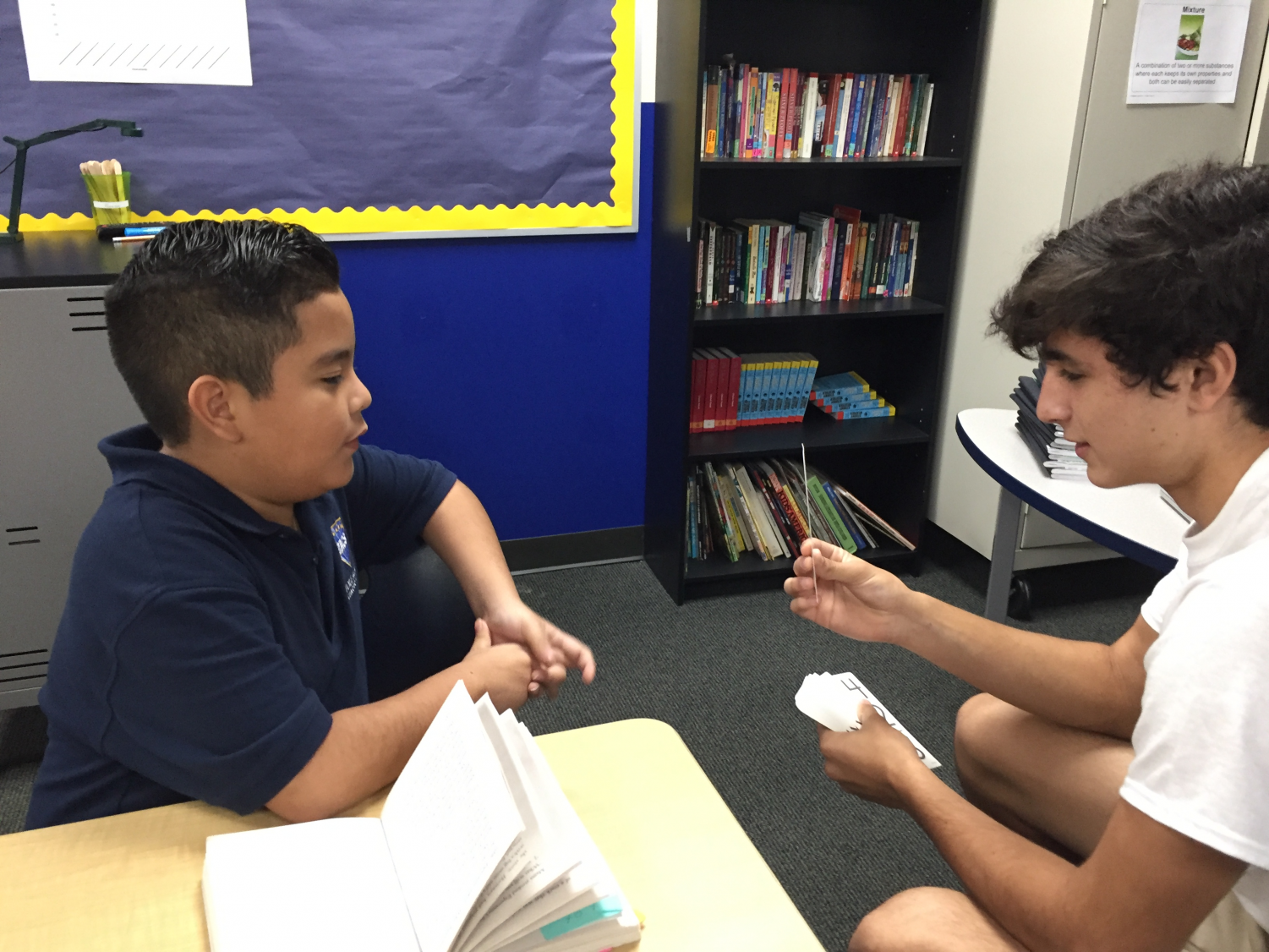 Freshman Chethan Shultz practices flashcards with a student at Etoile Academy.
