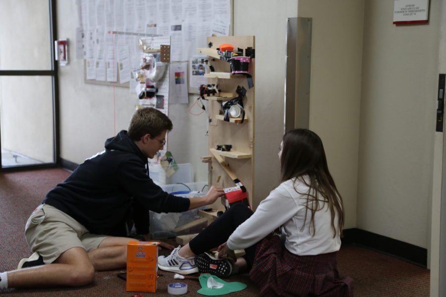 Emile Vlahos and Ava Leitner tinker with the mechanics of a Rube Goldberg machine.