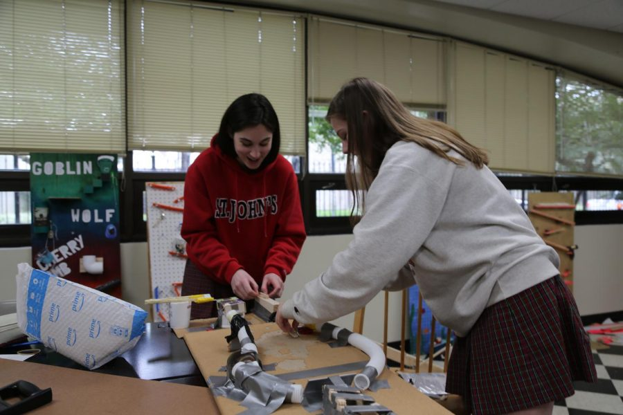Julia Rae and Abby Walker adjust the pipe on their Rube Goldberg machine.