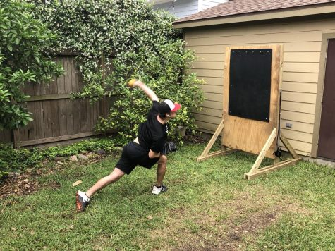 Hay throws a pitch in his backyard while in quarantine.