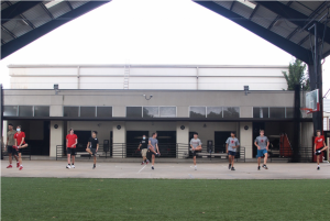 """The boys' volleyball team stretches underneath """"Big Red,"""" the outdoor basketball court."""