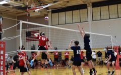 Boys' volleyball captain Jackson Peakes coils his arm to spike the ball past the Houston Volleyball Academy blockers.