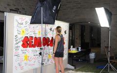 Caroline Pressler signs her name on the Senior Mural.