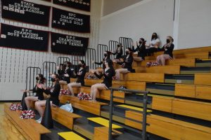 Varsity Cheer supports the basketball team while staying safely distanced.