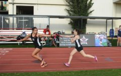 Junior Cici Calhoun passes the baton to senior Reese Ramirez in the 4x400m relay. The girls' track and field team placed sixth in the SPC Championship on May 8.