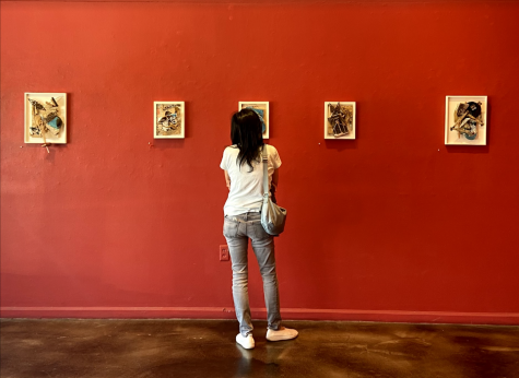 A woman studies the details of one of Havel's collages, Rafter. The pieces from left to right: Excuse My Scribbling, Square Deal, Rafter, Gothic Rupture and  Taking Measure.