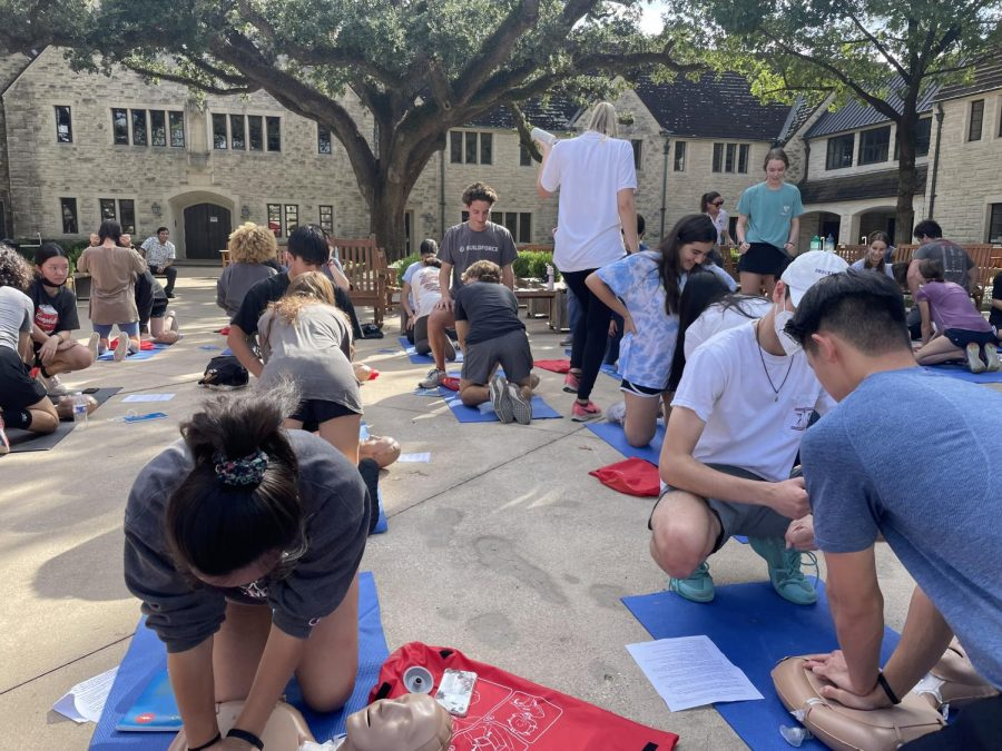 Seniors practice chest compressions on CPR dummies in the Plaza.